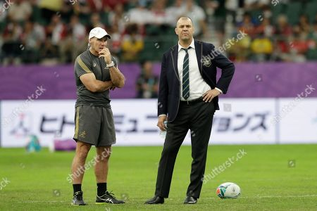 Australia coach Michael Cheika, right, watches as his team warm up before the Rugby World Cup quarterfinal match at Oita Stadium between England and Australia in Oita, Japan