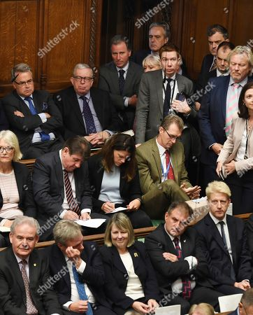 Lawmakers crowd the benches, with Oliver Letwin, top 3rd from left, and brother of the prime minister lawmaker Jo Johnson at bottom right, as they listen to Britain's Prime Minister Boris Johnson as he gives a Brexit statement to lawmakers inside the House of Commons, in London . Lawmakers are to be granted a chance to vote Saturday on the 'Oliver Letwin Amendment' to the Brexit deal, which may delay their final decision on Brexit