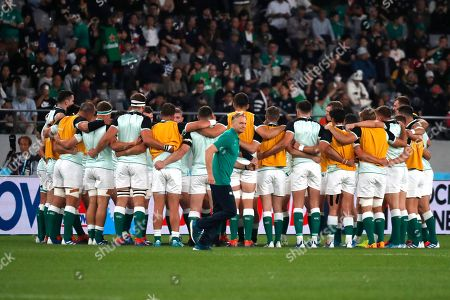 Ireland coach Joe Schmidt moves past his players ahead of the Rugby World Cup quarterfinal match at Tokyo Stadium between New Zealand and Ireland in Tokyo, Japan