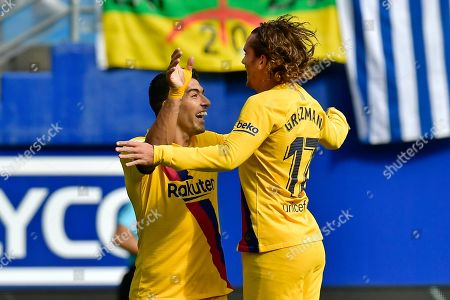 Barcelona's Antoine Griezmann, right, celebrates with Luis Suarez after scoring the opening goal during a Spanish La Liga soccer match between Eibar and FC Barcelona at the Ipurua stadium in Eibar, Spain