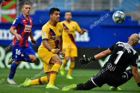 Barcelona's Luis Suarez tries to beat Eibar's goalkeeper Marko Dmitrovic during a Spanish La Liga soccer match between Eibar and FC Barcelona at the Ipurua stadium in Eibar, Spain