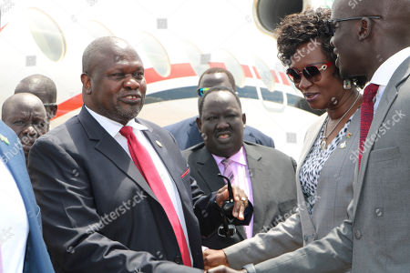 South Sudan opposition leader Riek Machar, left, is greeted by South Sudan officials as he returned to the country, Saturday, Oct.19, 2019, to meet with President Salva Kiir less than a month before their deadline to form a unity government after a five-year civil war. Macher's two-day visit includes a scheduled meeting with the U.S. ambassador to the United Nations, who arrives Sunday with a U.N. Security Council delegation