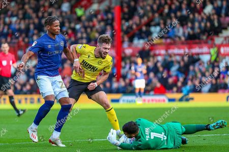 Stock Photo of Brentford goalkeeper David Raya Martin (1) makes a save from Millwall forward Tom Bradshaw (9) challenged by Brentford defender Julian Jeanvier (23) during the EFL Sky Bet Championship match between Brentford and Millwall at Griffin Park, London