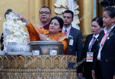 Nepal's President Bidhya Devi Bhandari (C) offers water to the Buddha as she visits the Shwedagon pagoda in Yangon, Myanmar, 19 October 2019. Nepal's president Bidhya Devi Bhandari is on a four-day visit to Myamar and met with Myanmar president and State Counselor Aung San Suu Kyi in Naypyitaw.