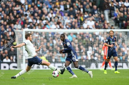Abdoulaye Doucoure of Watford passes a ball past the outstrecthed leg of Jan Vertonghen of Tottenham Hotspur