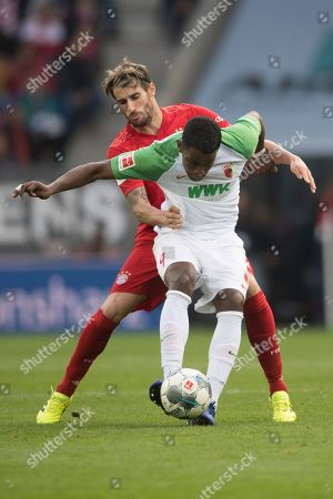 Augsburg's Sergio Cordova (front) in action against Bayern Munich's Javi Martinez (back) during the German Bundesliga soccer match between FC Augsburg and FC Bayern Munich in Augsburg, Germany, 19 October 2019.