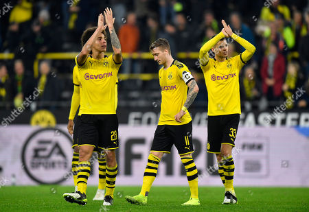 Stock Picture of Dortmund's scorer Marco Reus, center, leaves the pitch beside Axel Witsel, left, and Julian Weigl, right, after winning the German Bundesliga soccer match between Borussia Dortmund and Borussia Moenchengladbach in Dortmund, Germany