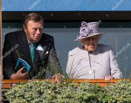 Queen Elizabeth II joined by trainer Nicky Henderson watches the parade ring from the balcony at the QIPCO Champions day.