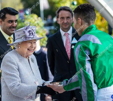Stock Picture of Queen Elizabeth II presents jockey Sean Levey with his trophy after winning the Queen Elizabeth II Stakes.