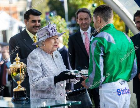 Stock Photo of Queen Elizabeth II presents jockey Sean Levey with his trophy after winning the Queen Elizabeth II Stakes.