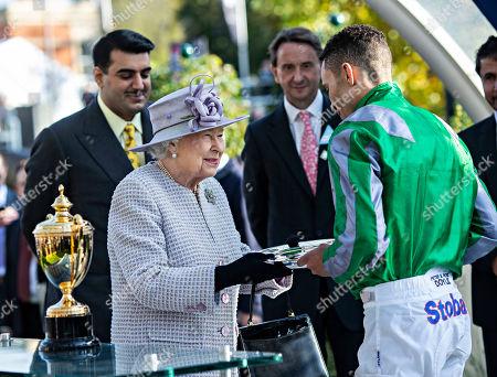 Queen Elizabeth II presents jockey Sean Levey with his trophy after winning the Queen Elizabeth II Stakes.