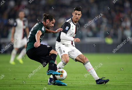Juventus' Cristiano Ronaldo, right, challenges for the ball with Bologna's Andrea Poli during a Serie A soccer match between Juventus and Bologna, at the Allianz stadium in Turin, Italy, Saturday, Oct.19, 2019