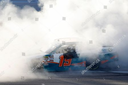 Brandon Jones (19) does a burnout after winning a NASCAR Xfinity Series auto race at Kansas Speedway in Kansas City, Kan