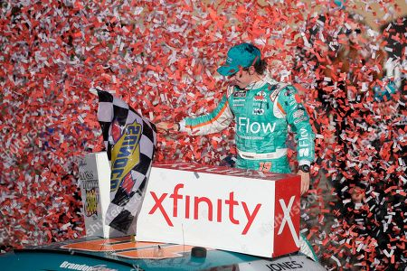 Brandon Jones celebrates in Victory Lane after winning a NASCAR Xfinity Series auto race at Kansas Speedway in Kansas City, Kan