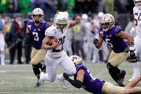 Travis Dye, Asa Turner. Oregon's Travis Dye (26) is tripped up by Washington's Asa Turner in the second half of an NCAA college football game, in Seattle. Oregon won 35-31
