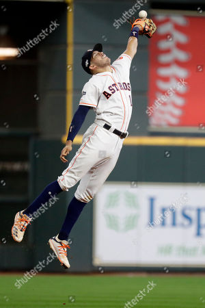 Houston Astros shortstop Carlos Correa knocks down a ball hit by New York Yankees' Aaron Judge during the seventh inning in Game 6 of baseball's American League Championship Series, in Houston. Judge was safe at first