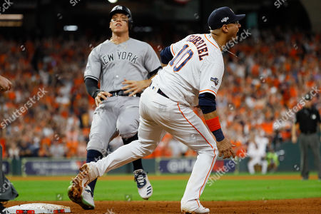 Houston Astros first baseman Yuli Gurriel, right, celebrates after New York Yankees' Aaron Judge is forced out at first for a double play to end the top of the seventh inning in Game 6 of baseball's American League Championship Series, in Houston
