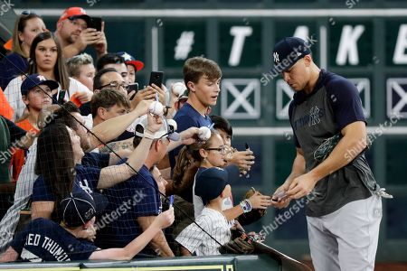 New York Yankees right fielder Aaron Judge signs autographs during batting practice before Game 6 of baseball's American League Championship Series against the Houston Astros, in Houston
