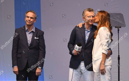 """Presidential candidate for """"Juntos Por el Cambio"""" party and Argentina's President Mauricio Macri, center, is kissed by his wife Juliana Awada, right, and his running-mate Miguel Angel Pichetto stands beside during a rally at """"9 de Julio"""" avenue in Buenos Aires, Argentina, . Argentina will hold its presidential election on Oct. 27"""