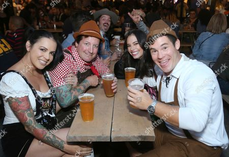"""Stock Image of Adam Devine, Chloe Bridges. Actor Adam Devine,from right, Chloe Bridges, and guests dressed in German traditional outfits have fun at the """"Oktoberfest HB"""" at the Old World German Restaurant, in Hiuntington Beach, Calif"""