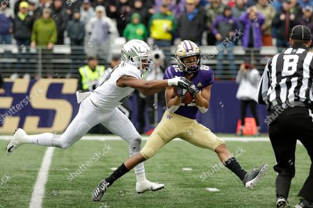 Washington's Jordan Chin, right, turns toward the goal line after catching a 48-yard touchdown pass as Oregon's Thomas Graham Jr. defends in the first half of an NCAA college football game, in Seattle
