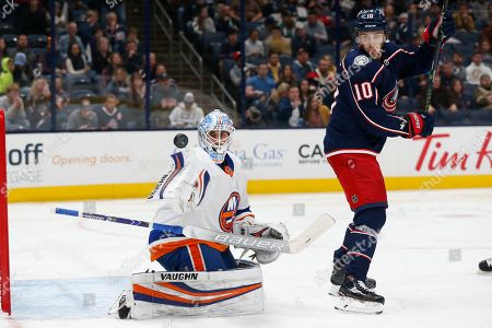 New York Islanders' Thomas Greiss, left, of Germany, makes a save in front of Columbus Blue Jackets' Alexander Wennberg, of Sweden, during the second period of an NHL hockey game, in Columbus, Ohio