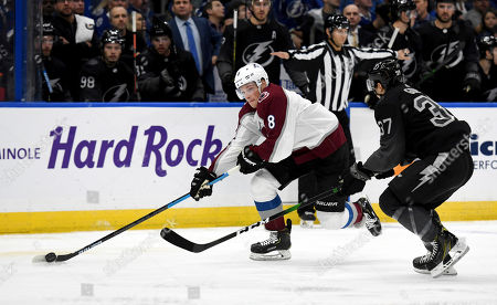 Colorado Avalanche defenseman Cale Makar (8) handles the puck against Tampa Bay Lightning center Yanni Gourde (37) during the first period of an NHL hockey game, in Tampa, Fla