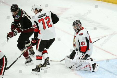As Arizona Coyotes right wing Brad Richardson (15) creates a screen in front of Ottawa Senators defenseman Thomas Chabot (72) the puck slips past Senators goaltender Craig Anderson (41) for a goal by Coyotes' Kyle Capobianco during the first period of an NHL hockey game, in Glendale, Ariz