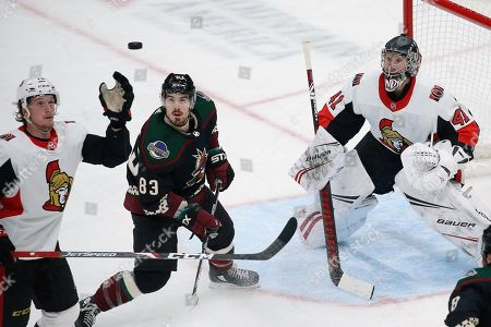 Stock Image of Ottawa Senators defenseman Thomas Chabot, left, reaches for the puck as Arizona Coyotes right wing Conor Garland (83) and Senators goaltender Craig Anderson (41) looks on during the third period of an NHL hockey game, in Glendale, Ariz