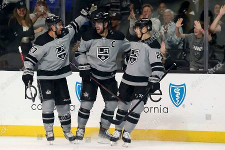Stock Photo of Los Angeles Kings center Anze Kopitar, center, of Slovenia, celebrates with defenseman Alec Martinez, left, and left wing Dustin Brown after scoring against the Calgary Flames during the second period of an NHL hockey game in Los Angeles