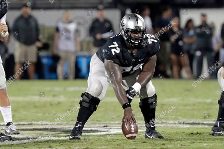 Central Florida offensive lineman Jordan Johnson centers the ball during the first half of an NCAA college football game against East Carolina, in Orlando, Fla