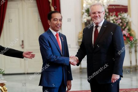 Joko Widodo, Scott Morrison. Indonesian President Joko Widodo, left, poses with Australian Prime Minister Scott Morrison for a photo during their meeting ahead of Widodo's inauguration, at Merdeka Palace in Jakarta, Indonesia