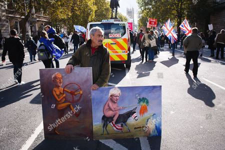 Political artist, Kaya Mar stands with two of his paintings at Whitehall during the protest