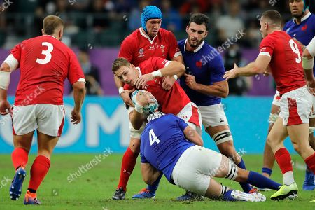 Wales' Liam Williams, center, is tackled by France's Bernard Le Roux during the Rugby World Cup quarterfinal match at Oita Stadium in Oita, Japan