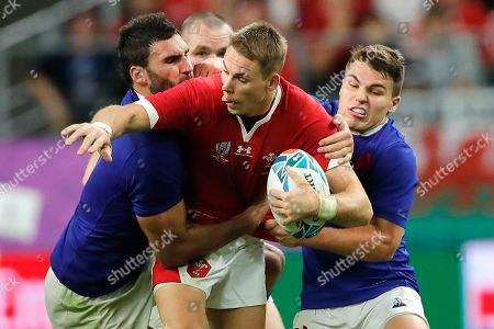 Wales' Liam Williams, center, is tackled by France's Antoine Dupont, right, during the Rugby World Cup quarterfinal match at Oita Stadium in Oita, Japan