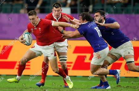 Wales' Liam Williams, left, fends off France's Camille Chat (16) during the Rugby World Cup quarterfinal match at Oita Stadium in Oita, Japan