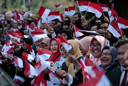 Palace staff wave Indonesian flags as the motorcade carrying President Joko Widodo leaves Merdeka Palace for the parliament building for his inauguration ceremony in Jakarta, Indonesia, . The country's popular president who rose from poverty and pledged to champion democracy, fight entrenched corruption and modernize the world's most populous Muslim-majority nation is to be sworn in for his final five-year term with a pledge to take bolder actions