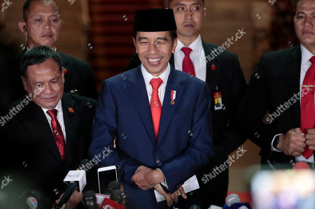 Indonesian President Joko Widodo, center, smiles as he speaks to the media upon arrival after his inauguration for his second term, at Merdeka Palace in Jakarta, Indonesia, . Widodo, who rose from poverty and pledged to champion democracy, fight entrenched corruption and modernize the world's most populous Muslim-majority nation, was sworn in Sunday for his second and final five-year term with a pledge to take bolder actions