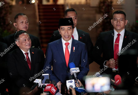 Stock Photo of Indonesian President Joko Widodo speaks to the media upon arrival from his inauguration for his second term, at Merdeka Palace in Jakarta, Indonesia, . Widodo, who rose from poverty and pledged to champion democracy, fight entrenched corruption and modernize the world's most populous Muslim-majority nation, was sworn in Sunday for his second and final five-year term with a pledge to take bolder actions