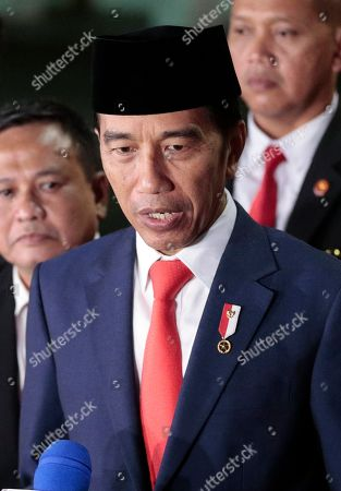 Indonesian President Joko Widodo speaks to the media upon arrival from his inauguration for his second term, at Merdeka Palace in Jakarta, Indonesia, . Widodo, who rose from poverty and pledged to champion democracy, fight entrenched corruption and modernize the world's most populous Muslim-majority nation, was sworn in Sunday for his second and final five-year term with a pledge to take bolder actions