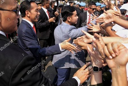 Indonesian President Joko Widodo, left, and his son, Gibran Rakabuming Raka, center, greet supporters prior to the inauguration for his second term, in Jakarta, Indonesia, . Indonesian President Joko Widodo, who rose from poverty and pledged to champion democracy, fight entrenched corruption and modernize the world's most populous Muslim-majority nation, was sworn in Sunday for his second and final five-year term with a pledge to take bolder actions