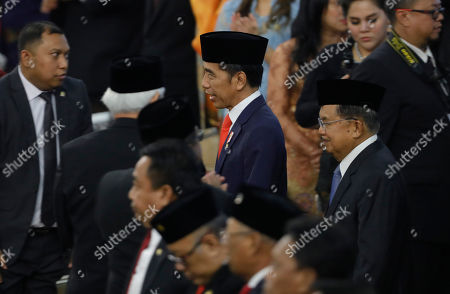 Indonesian President Joko Widodo, center, accompanied by his former Vice President Jusuf Kalla, right, are greeted by parliament members shortly before taking his presidential oath for his second five-year term during the Inauguration ceremony at the parliamentary building in Jakarta, Indonesia, . Indonesia's popular president who rose from poverty and pledged to champion democracy, fight entrenched corruption and modernize the world's most populous Muslim-majority nation is to be sworn in for his final five-year term