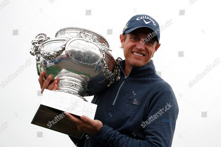 Stock Photo of Nicolas Colsaerts of Belgium poses for photographers with the trophy after winning the Amundi French Open, at Le Golf National in Saint-Quentin-en-Yvelines, outside Paris, France
