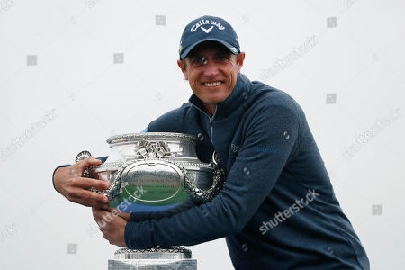 Nicolas Colsaerts of Belgium poses for photographers with the trophy after winning the Amundi French Open, at Le Golf National in Saint-Quentin-en-Yvelines, outside Paris, France