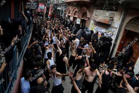 Pakistani Shiite Muslims beat their chests during a procession to mark the end of the forty day mourning period following the anniversary of the 7th century death of Imam Hussein, the Prophet Muhammad's grandson and one of Shiite Islam's most beloved saints, in Lahore, Pakistan