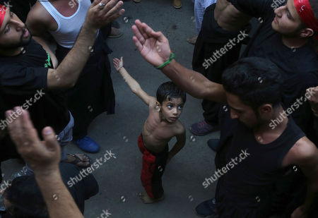 A Shiite Muslim child beats his chest next to his father during a procession to mark the end of the 40 day mourning period following the anniversary of the 7th century death of Imam Hussein, the Prophet Muhammad's grandson and one of Shiite Islam's most beloved saints, in Lahore, Pakistan