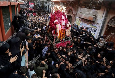 Stock Image of Pakistani Shiite Muslims participate in a procession to mark the end of the 40 day mourning period following the anniversary of the 7th century death of Imam Hussein, the Prophet Muhammad's grandson and one of Shiite Islam's most beloved saints, in Lahore, Pakistan