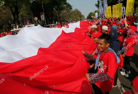 Supporters of Indonesian President Joko Widodo holds a large national Red-White flag during rally to celebrate his inauguration for his second term in Jakarta, Indonesia, . Indonesian President Joko Widodo, who rose from poverty and pledged to champion democracy, fight entrenched corruption and modernise the world's most populous Muslim-majority nation, was sworn in Sunday for his second and final five-year term with a pledge to take bolder actions