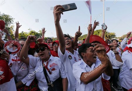 Stock Photo of Supporters of Indonesian President Joko Widodo holds a large national Red-White flag during rally to celebrate his inauguration for his second term in Jakarta, Indonesia, . Indonesian President Joko Widodo, who rose from poverty and pledged to champion democracy, fight entrenched corruption and modernise the world's most populous Muslim-majority nation, was sworn in Sunday for his second and final five-year term with a pledge to take bolder actions
