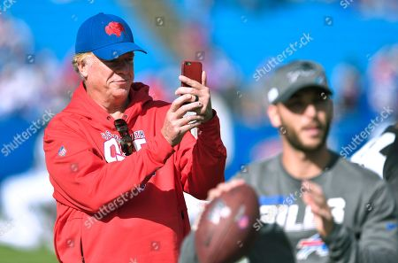 Actor Christopher McDonald photographs the teams as they warm up before an NFL football game between the Buffalo Bills and the Miami Dolphins, in Orchard Park, N.Y